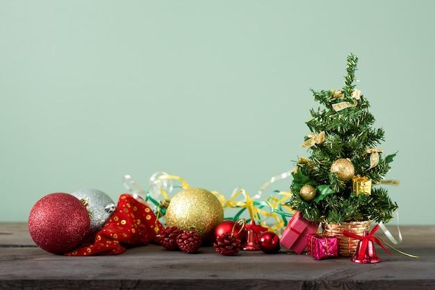 Kleiner weihnachtsbaum mit verzierungen auf einem dunklen holztisch.