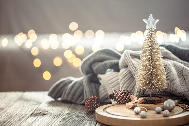 Kleiner weihnachtsbaum über weihnachtslichtern bokeh im haus auf holztisch mit pullover an einer wand und dekorationen.