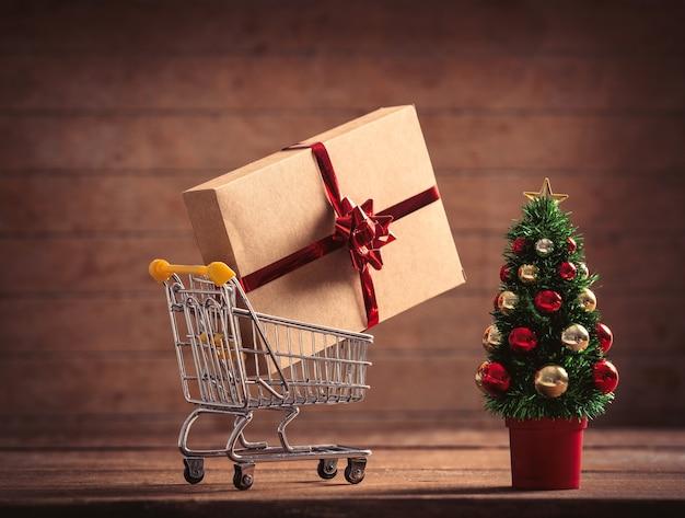 Kleiner weihnachtsbaum und geschenkbox im supermarktwagen auf holztisch und hintergrund