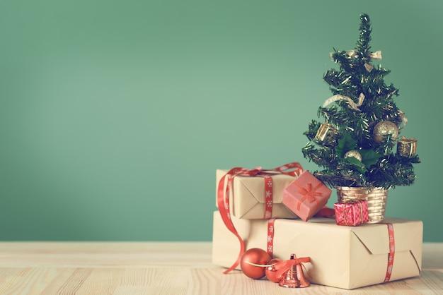 Kleiner weihnachtsbaum und kästen mit geschenken auf einem holztisch.