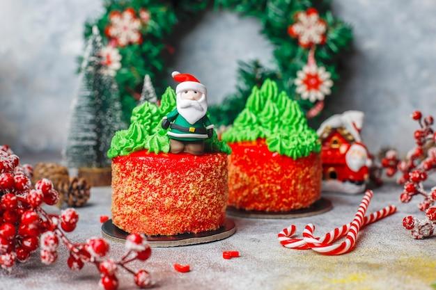 Kleiner weihnachtskuchen, verziert mit süßen figuren von weihnachtsbaum, weihnachtsmann und kerzen.