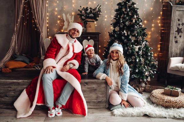 Kleiner weihnachtsmann, vater frost und schneewittchen lächelnd im weihnachtsinnenraum mit geschmücktem weihnachtsbaum.