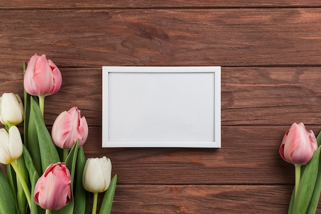 Kleiner weißer leerer rahmen mit den rosa und weißen tulpen auf hölzernem schreibtisch