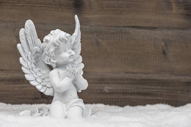 Kleiner weißer schutzengel im schnee auf hölzernem hintergrund. weihnachtsdekoration im vintage-stil