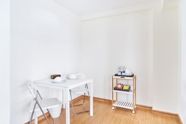 Kleiner weißer tisch mit klappstühlen im einfachen weißen reinraum des modernen lebens