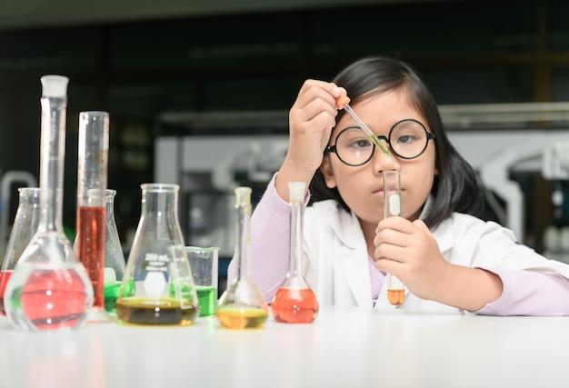 Kleiner wissenschaftler im laborkittel, der experiment bildet