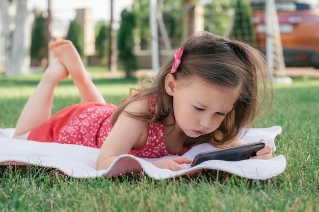 Kleines 3-4 mädchen in roter kleidung liegt auf einer decke auf grünem gras und schaut ins handy. kinder, die gadgets verwenden