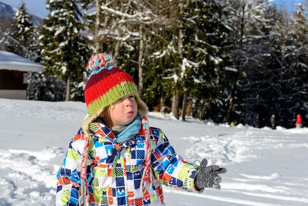 Kleines 3-jähriges kind, das im schnee spielt