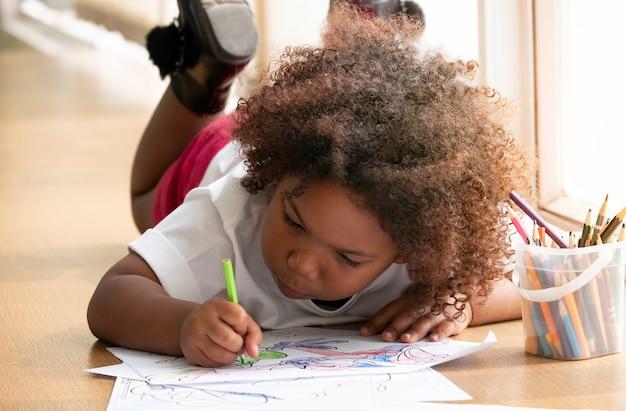 Kleines afrikanisches mädchen, das mit glück malt und zeichnet.