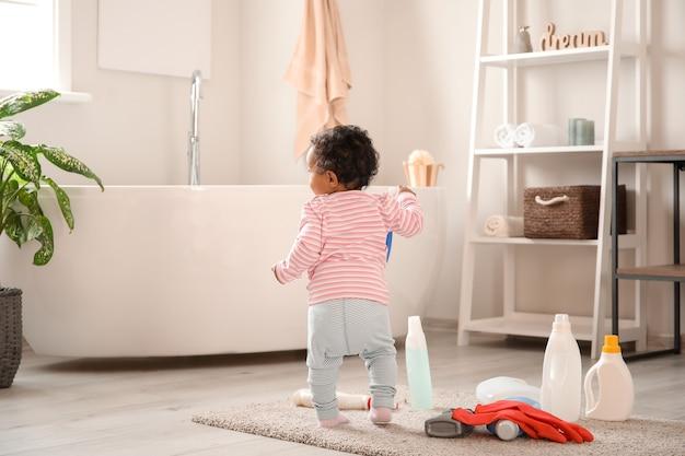 Kleines afroamerikanisches baby, das zu hause mit waschflüssigkeiten spielt. kind in gefahr