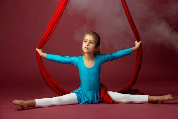 Kleines akrobatenmädchen, das spaltungen in der luft tut