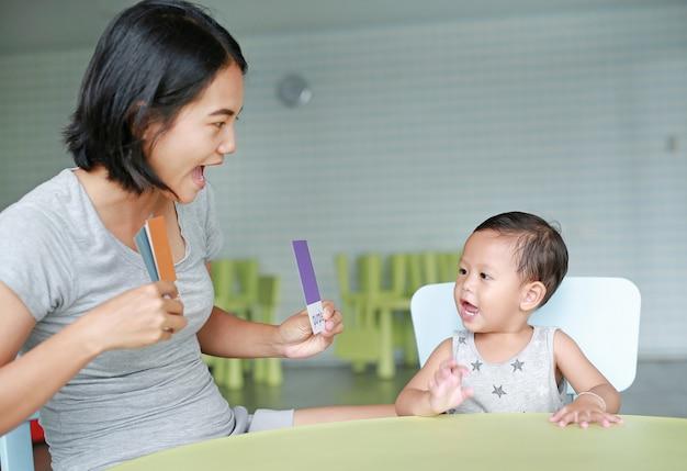 Kleines asiatisches baby und mutter, die grelle karte für entwicklung des rechten gehirns am spielzimmer spielt. fokus auf kindergesicht. kind lernen konzept.