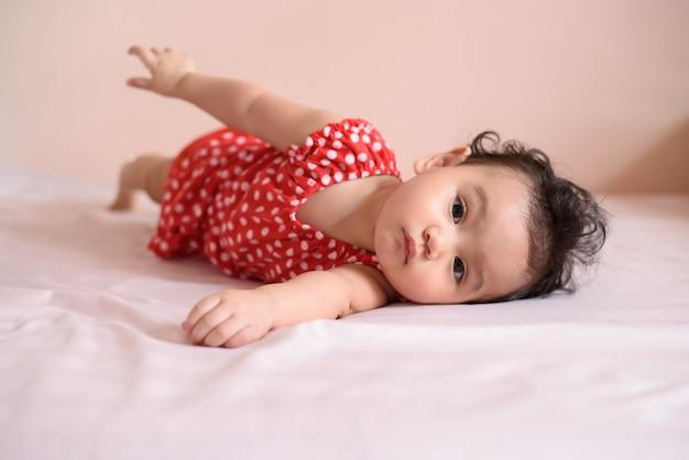 Kleines asiatisches gewelltes schwarzes haarbaby, ein süßes kleinkind in rot, das auf dem bett liegt und in die kamera schaut
