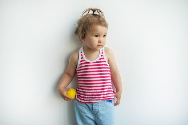 Kleines asiatisches kind auf weißem wandhintergrund.