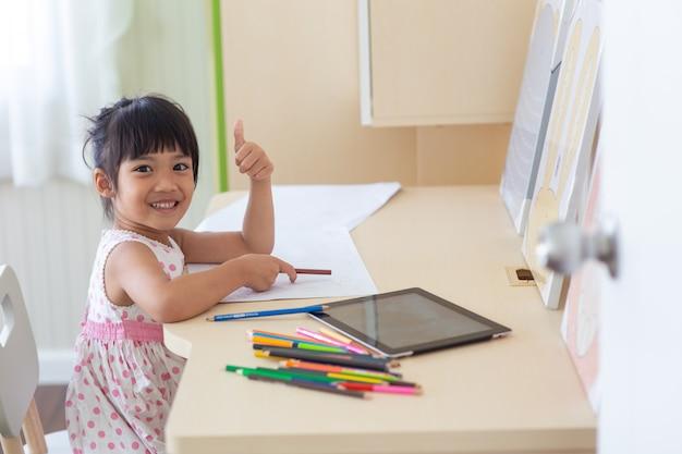 Kleines asiatisches kind, das einen bleistift verwendet, um auf notizbuch am schreibtisch zu schreiben