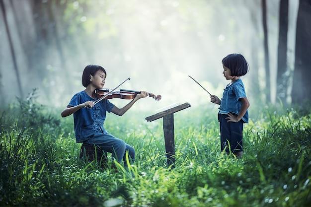 Kleines asiatisches kind, das violine an draußen spielt