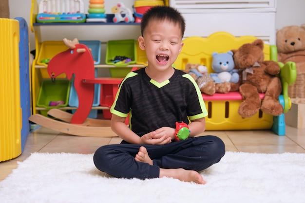Kleines asiatisches kind mit geschlossenen augen barfuß praktiziert yoga-meditation, um negative emotionen zu lindern