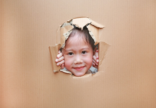 Kleines asiatisches kindermädchen, das durch loch auf pappe schaut.