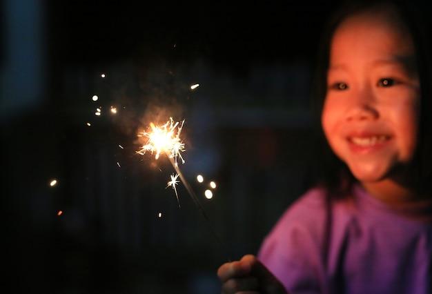 Kleines asiatisches kindermädchen genießen, kracher zu spielen. fokus auf feuer wunderkerzen.