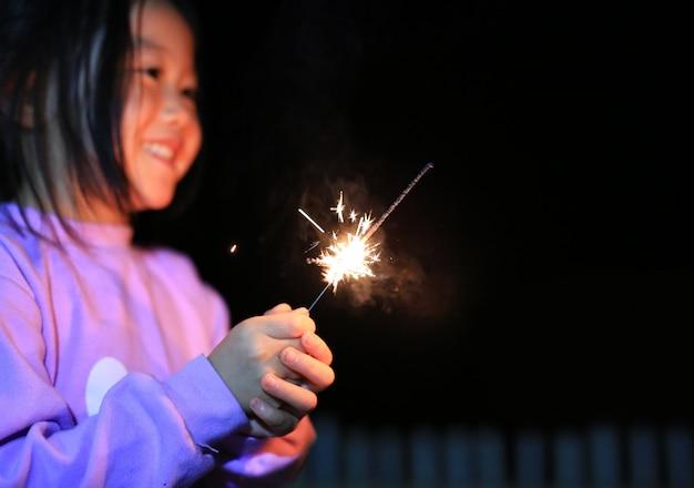 Kleines asiatisches kindermädchen genießen, kracher zu spielen
