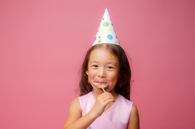 Kleines asiatisches mädchen, auf einer geburtstagsfeier, einem lutscher, auf einem rosa