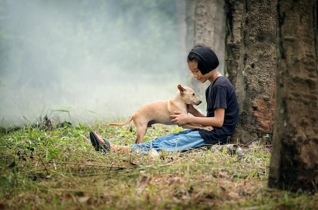 Kleines asiatisches mädchen, das allein auf grünem feld unter dem baum mit ihrem hund, im freien an der landschaft von thailand sitzt