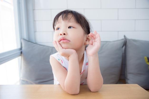 Kleines asiatisches mädchen, das allein sitzt und etwas in der schule denkt
