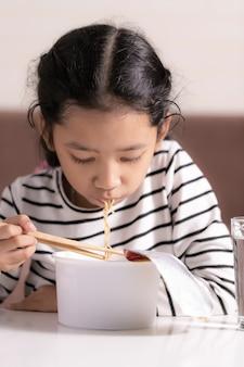 Kleines asiatisches mädchen, das am weißen tisch zum essen der flachen tiefe des ausgewählten fokus der sofortigen nudel von archiviert sitzt