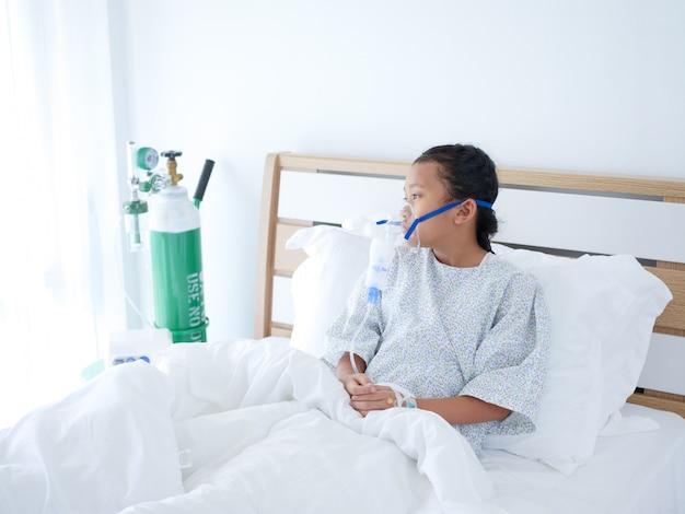 Kleines asiatisches mädchen, das auf bett im krankenhauszimmer mit sauerstoffmaske legt.