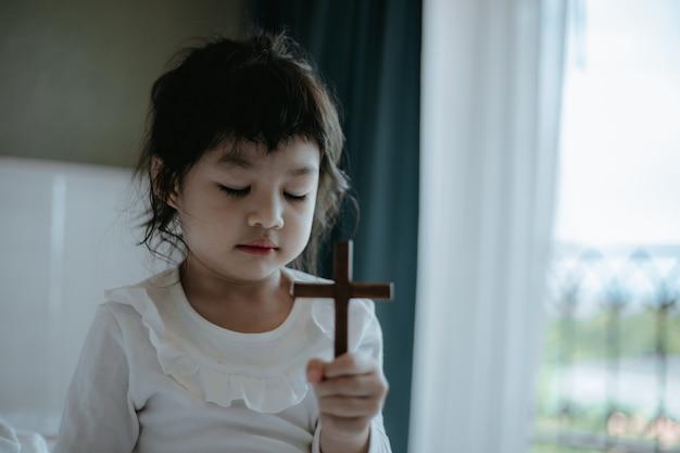 Kleines asiatisches mädchen, das betet und holzkreuz hält.