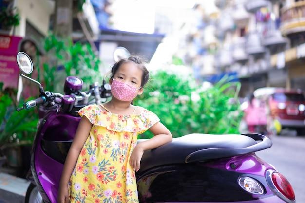 Kleines asiatisches mädchen, das eine maske gegen abenddämmerung und covid-19 im freien trägt