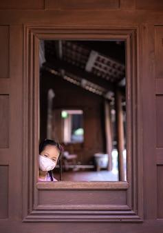 Kleines asiatisches mädchen, das eine maske gegen abenddämmerung und covid-19 nahe dem fenster trägt