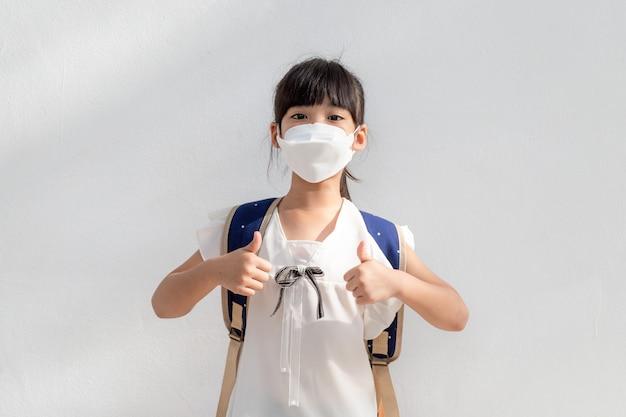 Kleines asiatisches mädchen, das eine maske trägt, um pm25 zu schützen und die geste mit dem daumen nach oben für gute luft im freien zu zeigen