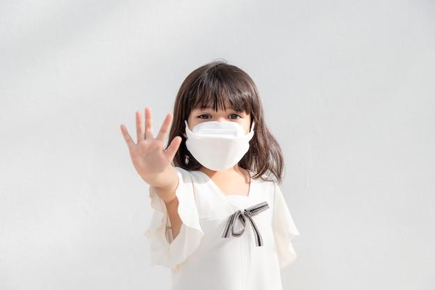 Kleines asiatisches mädchen, das eine maske zum schutz trägt, zeigt die geste der hände, um den ausbruch des coronavirus zu stoppen