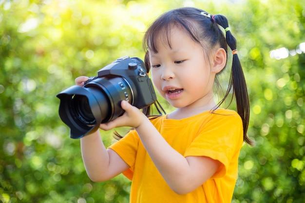 Kleines asiatisches mädchen, das foto durch kamera im park macht