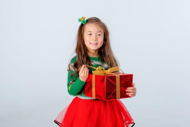 Kleines asiatisches mädchen, das geschenk auf weißem hintergrund des neuen jahres weihnachten hält