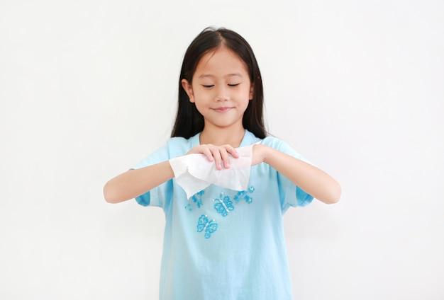 Kleines asiatisches mädchen, das hände durch feuchtes tuchgewebe reinigt