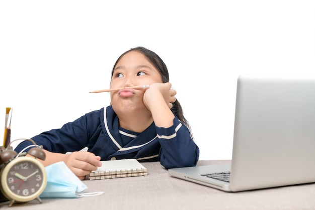 Kleines asiatisches mädchen, das hausaufgaben auf laptop macht