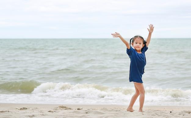 Kleines asiatisches mädchen, das ihre hand sagt auf wiedersehen auf dem strand wellenartig bewegt