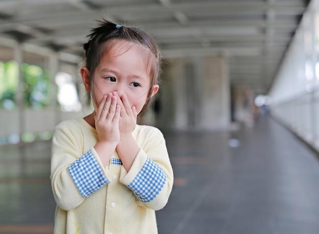 Kleines asiatisches mädchen, das ihren mund und nase mit ihren händen bedeckt.