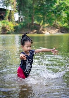 Kleines asiatisches mädchen, das im fluss mit wasserspritzen spielt