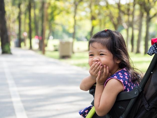 Kleines asiatisches mädchen, das in einem spaziergänger am allgemeinen park sitzt
