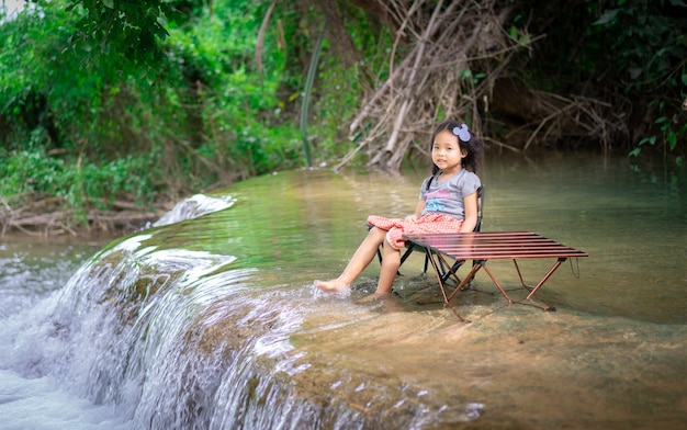 Kleines asiatisches mädchen, das in einem stuhl im wasserfall zwischen dem kampieren sitzt