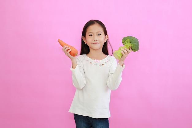 Kleines asiatisches mädchen, das karotte und brokkoli hält, die auf rosa stehen