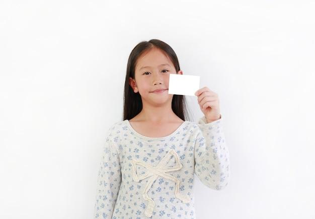 Kleines asiatisches mädchen, das leere weiße karte vor weißem hintergrund zeigt