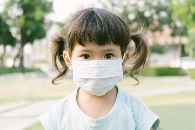 Kleines asiatisches mädchen, das maske trägt, um pm2.5 und coronavirus-konzept zu schützen