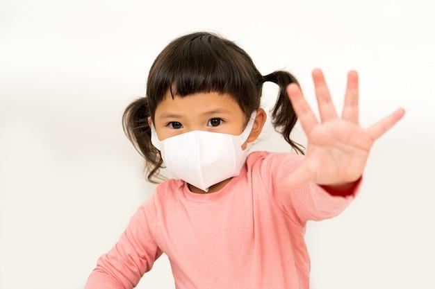 Kleines asiatisches mädchen, das maske trägt, um pm2.5 zu schützen und handstopp zu zeigen
