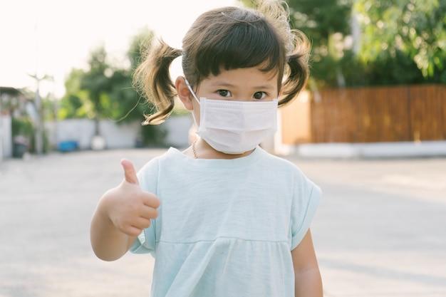 Kleines asiatisches mädchen, das maske zum schutz pm2.5 trägt und daumen hoch geste für gute luft im freien zeigt. luftverschmutzung pm2.5 und coronavirus-konzept