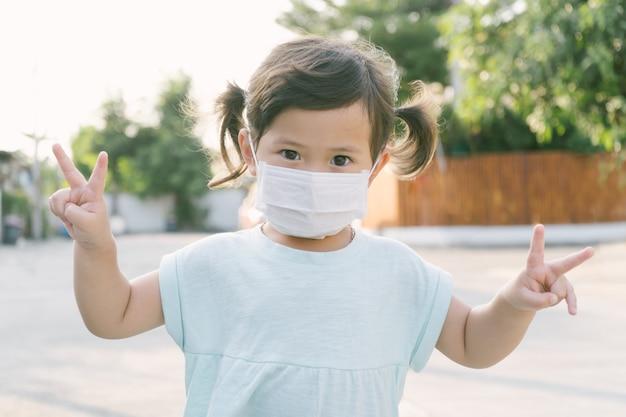 Kleines asiatisches mädchen, das maske zum schutz pm2.5 trägt und geste nummer zwei für gute luft im freien zeigt. luftverschmutzung pm2.5 und coronavirus-konzept
