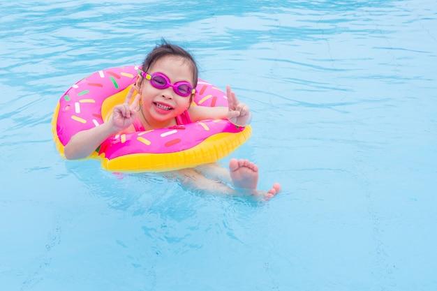 Kleines asiatisches mädchen, das mit ring im pool schwimmt